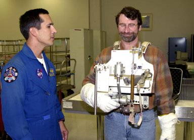 """KENNEDY SPACE CENTER, FLA. -- While astronaut John Herrington (left) looks on, Norm Abram tries on a tool carrier used in space. Abram is master carpenter of television?s """"This Old House"""" and """"The New Yankee Workshop."""" He is at KSC to film an episode of """"This Old House."""