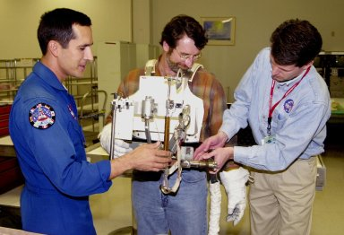 """KENNEDY SPACE CENTER, FLA. -- After trying on a tool carrier, master carpenter of television?s """"This Old House"""" and """"The New Yankee Workshop"""" Norm Abram (center) receives assistance from astronaut John Herrington (left) and Phil West (right), with Johnson Space Center. Abram is at KSC to film an episode of """"This Old House."""