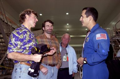 """KENNEDY SPACE CENTER, FLA. -- Steve Thomas (left) and Norm Abram (second from left), who are seen in the television series """"This Old House,"""" talk with astronaut John Herrington (right). In the background is Johnny Johnson, media escort. Abram is at KSC to film an episode of """"This Old House."""