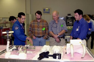 """KENNEDY SPACE CENTER, FLA. -- Astronaut John Herrington (left) shows tools and equipment used in space to Norm Abram, master carpenter of television?s """"This Old House"""" and """"The New Yankee Workshop."""" At right are two of the film crew with Abram. Abram is at KSC to film an episode of """"This Old House."""