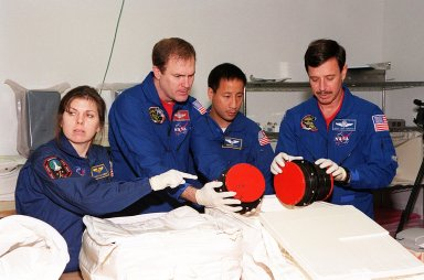 """KENNEDY SPACE CENTER, FLA. -- At SPACEHAB, in Cape Canaveral, the STS-101 crew inspect equipment and payload for their mission. From left to right are Mission Specialist Mary Ellen Weber (Ph.D.) , Commander James D. Halsell Jr., Mission Specialist Edward Tsang Lu and Pilot Scott J. """"Doc"""" Horowitz (Ph.D.). They are taking part in a Crew Equipment Interface Test, which gives them an opportunity to look over equipment and payloads that will fly on the mission. Space Shuttle Atlantis will be carrying the SPACEHAB Double Module, which carries internal logistics and resupply cargo for station outfitting. Launch of Atlantis on mission STS-101 is scheduled no earlier than April 13, 2000"""