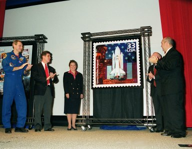 """One of a new series of U.S. Postage stamps, The 1980s, is unveiled at the KSC Visitors Complex. The stamp, shown here, is the Space Shuttle Columbia, first launched in April 1981. This collection of stamps is the ninth in the Post Office's """"Celebrate the Century"""" commemorative series honoring the last 100 years of American history. Taking part in the """"First Day of Issue Ceremony"""" are (left to right) astronaut Richard Linnehan, U.S. Representative, 15th Congressional District, Dave Weldon, U.S. Postal Service District Manager Viki Brennan, Center Director Roy Bridges and President of the Visitor Complex Rick Abramson"""