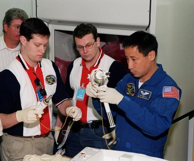KENNEDY SPACE CENTER, FLA. -- At SPACEHAB, in Cape Canaveral, technicians help STS-101 Mission Specialist Edward Tsang Lu become familiar with equipment for the mission. Lu and other members of the crew are taking part in a Crew Equipment Interface Test, which gives them an opportunity to look over equipment and payloads that will fly on the mission. Space Shuttle Atlantis will be carrying the SPACEHAB Double Module, which carries internal logistics and resupply cargo for station outfitting. Launch of Atlantis on mission STS-101 is scheduled no earlier than April 13, 2000