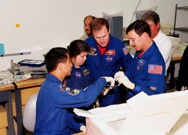 """KENNEDY SPACE CENTER, FLA. -- At SPACEHAB, in Cape Canaveral, the STS-101 crew inspect equipment and payload for their mission. From left to right are Mission Specialist Edward Tsang Lu, Mary Ellen Weber (Ph.D.), Commander James D. Halsell Jr. and Pilot Scott J. """"Doc"""" Horowitz (Ph.D). are taking part in a Crew Equipment Interface Test, which gives them an opportunity to look over equipment and payloads that will fly on the mission. Space Shuttle Atlantis will be carrying the SPACEHAB Double Module, which carries internal logistics and resupply cargo for station outfitting. Launch of Atlantis on mission STS-101 is scheduled no earlier than April 13, 2000"""