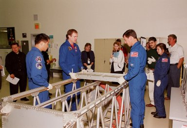 """KENNEDY SPACE CENTER, FLA. -- At SPACEHAB, in Cape Canaveral, members of the STS-101 crew inspect equipment and payload for their mission. From left to right (in uniform) are Mission Specialist Edward Tsang Lu, Commander James D. Halsell Jr., Pilot Scott J. """"Doc"""" Horowitz (Ph.D) and Mission Specialist Mary Ellen Weber (Ph.D.). They are taking part in a Crew Equipment Interface Test, which gives them an opportunity to look over equipment and payloads that will fly on the mission. Space Shuttle Atlantis will be carrying the SPACEHAB Double Module, which carries internal logistics and resupply cargo for station outfitting. Launch of Atlantis on mission STS-101 is scheduled no earlier than April 13, 2000"""