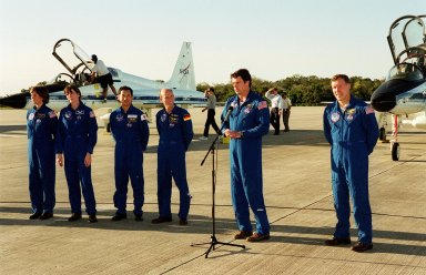 After their arrival at the Shuttle Landing Facility aboard T-38 training jet aircraft (background), the STS-99 crew talk to the media. From left are Mission Specialists Janice Voss (Ph.D.), Janet Lynn Kavandi (Ph.D.), Mamoru Mohri, who is with the National Space Development Agency (NASDA) of Japan, and Gerhard Thiele, with the European Space Agency, Commander Kevin Kregel (at microphone) and Pilot Dominic Gorie. The crew are here to take part in a Terminal Countdown Demonstration Test (TCDT), which provides simulated countdown exercises, emergency egress training, and opportunities to inspect the mission payloads in the orbiter's payload bay. STS-99 is the Shuttle Radar Topography Mission, which will chart a new course, using two antennae and a 200-foot-long section of space station-derived mast protruding from the payload bay to produce unrivaled 3-D images of the Earth's surface. The result of the Shuttle Radar Topography Mission could be close to 1 trillion measurements of the Earth's topography. Besides contributing to the production of better maps, these measurements could lead to improved water drainage modeling, more realistic flight simulators, better locations for cell phone towers, and enhanced navigation safety. Launch of Endeavour on the 11-day mission is scheduled for Jan. 31 at 12:47 p.m. EST
