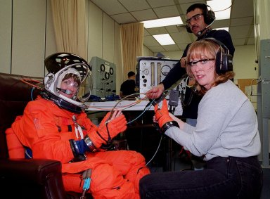 In the Operations and Checkout Building, STS-99 Mission Specialist Janet Lynn Kavandi (Ph.D.) is helped by a suit technician during flight crew equipment fit check prior to her trip to Launch Pad 39A. The crew is taking part in Terminal Countdown Demonstration Test (TCDT) activities that provide the crew with simulated countdown exercises, emergency egress training, and opportunities to inspect the mission payloads in the orbiter's payload bay. STS-99 is the Shuttle Radar Topography Mission, which will chart a new course, using two antennae and a 200-foot-long section of space station-derived mast protruding from the payload bay to produce unrivaled 3-D images of the Earth's surface. The result of the Shuttle Radar Topography Mission could be close to 1 trillion measurements of the Earth's topography. Besides contributing to the production of better maps, these measurements could lead to improved water drainage modeling, more realistic flight simulators, better locations for cell phone towers, and enhanced navigation safety. Launch of Endeavour on the 11-day mission is scheduled for Jan. 31 at 12:47 p.m. EST