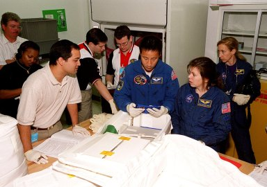 KENNEDY SPACE CENTER, FLA. -- With help from technicians at SPACEHAB, in Cape Canaveral, members of the STS-101 crew take part in a Crew Equipment Interface Test, which gives them an opportunity to look over equipment and payloads that will fly on the mission. In the center is Mission Specialist Edward Tsang Lu; at right is Mission Specialist Mary Ellen Weber (Ph.D.); in the background right is astronaut Marsha Ivins, who is assigned to mission STS-98 and is a veteran of four space flights. Her last flight, STS-81, including docking with the Russian Mir, and carrying the SPACEHAB double module to transfer tons of food and other cargo. On mission STS-101, Space Shuttle Atlantis will also be carrying the SPACEHAB Double Module, which will carry internal logistics and resupply cargo for station outfitting. Launch of Atlantis is scheduled no earlier than April 13, 2000