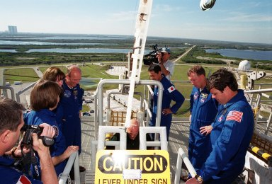 KENNEDY SPACE CENTER, Fla. -- Near the bunker at Launch Pad 39A, STS-99 Mission Specialists Janice Voss (Ph.D.), Gerhard Thiele and Mamoru Mohri check out the slidewire basket used for emergency egress. The crew are taking part in Terminal Countdown Demonstration Test activities, which provide them with simulated countdown exercises, emergency egress training, and opportunities to inspect the mission payloads in the orbiter's payload bay. Thiele is with the European Space Agency and Mohri is with the National Space Development Agency (NASDA) of Japan. STS-99 is the Shuttle Radar Topography Mission, which will chart a new course, using two antennae and a 200-foot-long section of space station-derived mast protruding from the payload bay to produce unrivaled 3-D images of the Earth's surface. The result of the Shuttle Radar Topography Mission could be close to 1 trillion measurements of the Earth's topography. Besides contributing to the production of better maps, these measurements could lead to improved water drainage modeling, more realistic flight simulators, better locations for cell phone towers, and enhanced navigation safety. Launch of Endeavour on the 11-day mission is scheduled for Jan. 31 at 12:47 p.m. EST