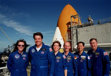 KENNEDY SPACE CENTER, Fla. -- At the 167-foot level of the Fixed Service Structure on Launch Pad 39A, the STS-99 crew pose for a photograph during Terminal Countdown Demonstration Test (TCDT) activities. Standing left to right are Mission Specialist Janet Lynn Kavandi (Ph.D.), Commander Kevin Kregel, Mission Specialists Janice Voss (Ph.D.), Gerhard Thiele and Mamoru Mohri, and Pilot Dominic Gorie. Thiele is with the European Space Agency and Mohri is with the National Space Development Agency (NASDA) of Japan. Behind them are visible the top of a solid rocket booster (white) and external tank (orange). The TCDT provides the crew with simulated countdown exercises, emergency egress training, and opportunities to inspect the mission payloads in the orbiter's payload bay. STS-99 is the Shuttle Radar Topography Mission, which will chart a new course, using two antennae and a 200-foot-long section of space station-derived mast protruding from the payload bay to produce unrivaled 3-D images of the Earth's surface. The result of the Shuttle Radar Topography Mission could be close to 1 trillion measurements of the Earth's topography. Besides contributing to the production of better maps, these measurements could lead to improved water drainage modeling, more realistic flight simulators, better locations for cell phone towers, and enhanced navigation safety. Launch of Endeavour on the 11-day mission is scheduled for Jan. 31 at 12:47 p.m. EST