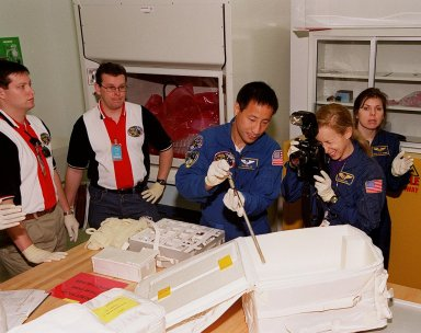 KENNEDY SPACE CENTER, FLA. -- At SPACEHAB, in Cape Canaveral, members of the STS-101 crew are taking part in a Crew Equipment Interface Test, which gives them an opportunity to look over equipment and payloads that will fly on the mission. At center is Mission Specialist Edward Tsang Lu; at right is Mission Specialist Mary Ellen Weber (Ph.D.). Between the, holding the camera, is astronaut Marsha Ivins, who is assigned to mission STS-98. On mission STS-101, Space Shuttle Atlantis will be carrying the SPACEHAB Double Module, which carries internal logistics and resupply cargo for station outfitting. Launch of Atlantis is scheduled no earlier than April 13, 2000