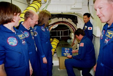 Inside the White Room attached to the Fixed Service Structure on Launch Pad 39A, STS-99 Commander Kevin Kregel gets ready to place a sign identifying the mission at the entrance to the orbiter Endeavour. Other crew members gathered around are (left to right) Mission Specialists Janice Voss (Ph.D.), Gerhard Thiele, Janet Lynn Kavandi (Ph.D.) and Mamoru Mohri (behind Kregel), and Pilot Dominic Gorie (at right). Thiele is with the European Space Agency and Mohri is with the National Space Development Agency (NASDA) of Japan. The crew are taking part in Terminal Countdown Demonstration Test activities, which provide them with simulated countdown exercises, emergency egress training, and opportunities to inspect the mission payloads in the orbiter's payload bay. STS-99 is the Shuttle Radar Topography Mission, which will chart a new course, using two antennae and a 200-foot-long section of space station-derived mast protruding from the payload bay to produce unrivaled 3-D images of the Earth's surface. The result of the Shuttle Radar Topography Mission could be close to 1 trillion measurements of the Earth's topography. Besides contributing to the production of better maps, these measurements could lead to improved water drainage modeling, more realistic flight simulators, better locations for cell phone towers, and enhanced navigation safety. Launch of Endeavour on the 11-day mission is scheduled for Jan. 31 at 12:47 p.m. EST