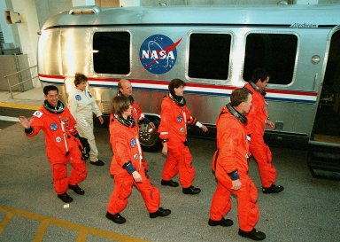"""In their orange flight suits, the STS-99 crew head toward the """"astrovan"""" that will take them to Launch Pad 39A for a simulated countdown exercise. From left to right are Mission Specialists Mamoru Mohri (waving), Gerhard Thiele, Janice Voss (Ph.D.) and Janet Lynn Kavandi (Ph.D.), Pilot Dominic Gorie and Commander Kevin Kregel. Mohri is with the National Space Development Agency (NASDA) of Japan and Thiele is with the European Space Agency. The crew are taking part in Terminal Countdown Demonstration Test activities, which provide them with simulated countdown exercises, emergency egress training, and opportunities to inspect the mission payloads in the orbiter's payload bay. STS-99 is the Shuttle Radar Topography Mission, which will chart a new course, using two antennae and a 200-foot-long section of space station-derived mast protruding from the payload bay to produce unrivaled 3-D images of the Earth's surface. The result of the Shuttle Radar Topography Mission could be close to 1 trillion measurements of the Earth's topography. Besides contributing to the production of better maps, these measurements could lead to improved water drainage modeling, more realistic flight simulators, better locations for cell phone towers, and enhanced navigation safety. Launch of Endeavour on the 11-day mission is scheduled for Jan. 31 at 12:47 p.m. EST"""
