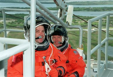 KENNEDY SPACE CENTER, Fla. -- At Launch Pad 39A, STS-99 Mission Specialists Gerhard Thiele (Ph.D.), of the European Space Agency (in front), and Janet Kavandi (Ph.D.) prepare to practice emergency egress procedures with a slidewire basket. Seven slidewires, with flatbottom baskets suspended from each wire, extend from the Fixed Service Structure at the orbiter access arm level. These baskets could provide an escape route for the astronauts until the final 30 seconds of the countdown in case of an emergency. The crew is taking part in Terminal Countdown Demonstration Test (TCDT) activities that provide the crew with simulated countdown exercises, emergency egress training, and opportunities to inspect the mission payloads in the orbiter's payload bay. STS-99 is the Shuttle Radar Topography Mission, which will chart a new course, using two antennae and a 200-foot-long section of space station-derived mast protruding from the payload bay to produce unrivaled 3-D images of the Earth's surface. The result of the Shuttle Radar Topography Mission could be close to 1 trillion measurements of the Earth's topography. Besides contributing to the production of better maps, these measurements could lead to improved water drainage modeling, more realistic flight simulators, better locations for cell phone towers, and enhanced navigation safety. Launch of Endeavour on the 11-day mission is scheduled for Jan. 31 at 12:47 p.m. EST.