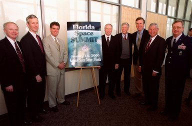 Before the start of the First Florida Space Summit, participants gather around the poster. From left are Center Director Roy Bridges, Representative Jim Davis, Representative Dave Weldon, NASA Administrator Dan Goldin, Senator Connie Mack, Governor Jeb Bush, Senator Bob Graham and 45th Space Wing Commander Brig. Gen. Donald Pettit. The summit, which was held at the Kennedy Space Center Visitor Complex, featured key state officials and aerospace companies to discuss the future of space as it relates to the State of Florida. Moderated by Bridges, the event also included State Senator Patsy Kurth, State Senator Charlie Bronson, and State Representative Randy Ball