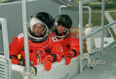 KENNEDY SPACE CENTER, Fla. -- At Launch Pad 39A, STS-99 Mission Specialists Mamoru Mohri (Ph.D.), who is with the National Space Development Agency (NASDA) of Japan, and Janice Voss (Ph.D.) practice emergency egress procedures in a slidewire basket. Seven slidewires, with flatbottom baskets suspended from each wire, extend from the Fixed Service Structure at the orbiter access arm level. These baskets could provide an escape route for the astronauts until the final 30 seconds of the countdown in case of an emergency. The crew is taking part in Terminal Countdown Demonstration Test (TCDT) activities that provide the crew with simulated countdown exercises, emergency egress training, and opportunities to inspect the mission payloads in the orbiter's payload bay. STS-99 is the Shuttle Radar Topography Mission, which will chart a new course, using two antennae and a 200-foot-long section of space station-derived mast protruding from the payload bay to produce unrivaled 3-D images of the Earth's surface. The result of the Shuttle Radar Topography Mission could be close to 1 trillion measurements of the Earth's topography. Besides contributing to the production of better maps, these measurements could lead to improved water drainage modeling, more realistic flight simulators, better locations for cell phone towers, and enhanced navigation safety. Launch of Endeavour on the 11-day mission is scheduled for Jan. 31 at 12:47 p.m. EST
