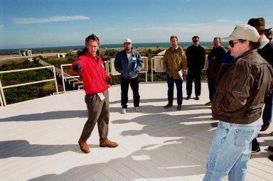 On top of the block house at Launch Complex 34, representatives from environmental and Federal agencies hear from Laymon Gray, with Florida State University, about the environmental research project that involves the Department of Defense, Environmental Protection Agency, Department of Energy and NASA in a groundwater cleanup effort. Concentrations of trichloroethylene solvent have been identified in the soil at the complex as a result of cleaning methods for rocket parts during the Apollo Program, which used the complex, in the 60s. The group formed the Interagency NDAPL Consortium (IDC) to study three contamination cleanup technologies: Six Phase Soil Heating, Steam Injection and In Situ Oxidation with Potassium Permanganate. All three methods may offer a way to remove the contaminants in months instead of decades. In the background (left) can be seen the cement platform and walkway from the block house to the pad. Beyond it is the Atlantic Ocean. KSC hosted a two-day conference that presented information and demonstrations of the three technologies being tested at the site