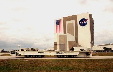 One of two new payload transporters for Kennedy Space Center moves past the Vehicle Assembly Building (left) and Launch Control Center (right) after being unloaded from a barge at Port Canaveral. The transporters, manufactured by the KAMAG Transporttechnick, GmbH, of Ulm, Germany, are replacing the existing Payload Canister Transporter system, which is 20 years old. Each transporter is 65 feet long and 22 feet wide and has 24 tires divided between its two axles. The transporter travels 10 miles per hour unloaded, 5 miles per hour when loaded; it weighs up to 172,000 pounds when the canister with payloads rides atop. The transporters will be outfitted with four subsystems for monitoring the environment inside the canister during the payload moves: the Electrical Power System, Environmental Control System, Instrumentation and Communications System, and the Fluids and Gases System. Engineers and technicians are being trained on the transporter's operation and maintenance