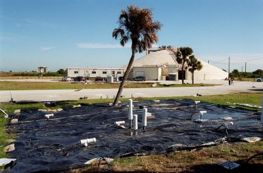 At Launch Complex 34, the Six-Phase Soil Heating site that is involved in a groundwater cleanup project can be seen. The project involves the Department of Defense, Environmental Protection Agency, Department of Energy and NASA. Concentrations of trichloroethylene solvent have been identified in the soil at the complex as a result of cleaning methods for rocket parts during the Apollo Program, which used the complex, in the 60s. The group formed the Interagency NDAPL Consortium (IDC) to study three contamination cleanup technologies: Six-Phase Soil Heating, Steam Injection and In Situ Oxidation with Potassium Permanganate. All three methods may offer a way to remove the contaminants in months instead of decades. In the background is the block house for the complex. KSC hosted a two-day conference that presented information and demonstrations of the three technologies being tested at the site