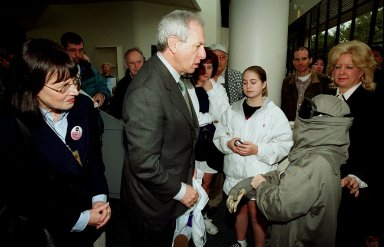 NASA Administrator Dan Goldin (center) greets 10-year-old Jonathan Pierce (right), who is garbed in a protective cooling suit designed by NASA. In the background, between them, are Jonathan's mother, Penny; his grandfather, John Janocka; and his sister, Jaimie.. At left is Mrs. Goldin. Jonathan suffers from erythropoietic protoporphyria, a rare condition that makes his body unable to withstand ultraviolet rays. The suit allows him to be outside during the day, which would otherwise be impossible. Jonathan's trip was funded by the Make-A-Wish Foundation and included a visit to Disney World. He and his family were among a dozen VIPs at KSC to view the launch of STS-99