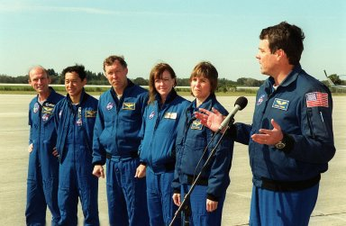 After arriving at KSC's Shuttle Landing Facility, the STS-99 crew pause to greet the media and Commander Kevin Kregel (right) introduces his crew: (from left) Mission Specialists Gerhard Thiele (Ph.D.) and Mamoru Mohri (Ph.D.); Pilot Dominic Gorie; and Mission Specialists Janet Lynn Kavandi (Ph.D.) and Janice Voss (Ph.D.). Thiele is with the European Space Agency and Mohri is with the National Space Development Agency (NASDA) of Japan. Over the next few days, the crew will review mission procedures, conduct test flights in the Shuttle Training Aircraft and undergo routine preflight medical exams. STS-99 is the Shuttle Radar Topography Mission, which will chart a new course, using two antennae and a 200-foot-long section of space station-derived mast protruding from the payload bay to produce unrivaled 3-D images of the Earth's surface. The result of the Shuttle Radar Topography Mission could be close to 1 trillion measurements of the Earth's topography. Besides contributing to the production of better maps, these measurements could lead to improved water drainage modeling, more realistic flight simulators, better locations for cell phone towers, and enhanced navigation safety. Launch of Endeavour is scheduled for Jan. 31 at 12:47 p.m. EST