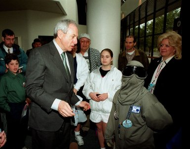 NASA Administrator Dan Goldin (center) talks to 10-year-old Jonathan Pierce (right), who is garbed in a protective cooling suit designed by NASA. In the background, between them, are Jonathan's mother, Penny; his grandfather, John Janocka; and his sister, Jaimie. At left is Mrs. Goldin. Jonathan suffers from erythropoietic protoporphyria, a rare condition that makes his body unable to withstand ultraviolet rays. The suit allows him to be outside during the day, which would otherwise be impossible. Jonathan's trip was funded by the Make-A-Wish Foundation and included a visit to Disney World. He and his family were among a dozen VIPs at KSC to view the launch of STS-99