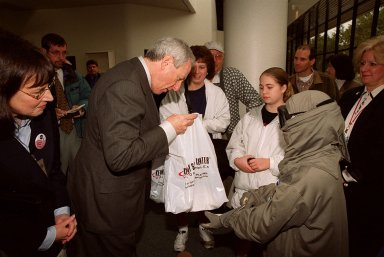 NASA Administrator Dan Goldin (center) presents a bag of special gifts to 10-year-old Jonathan Pierce (right), who is garbed in a protective cooling suit designed by NASA. In the background, between them, are Jonathan's mother, Penny; his grandfather, John Janocka; and his sister, Jaimie.. At left is Mrs. Goldin. Jonathan suffers from erythropoietic protoporphyria, a rare condition that makes his body unable to withstand ultraviolet rays. The suit allows him to be outside during the day, which would otherwise be impossible. Jonathan's trip was funded by the Make-A-Wish Foundation and included a visit to Disney World. He and his family were among a dozen VIPs at KSC to view the launch of STS-99