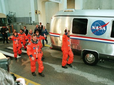 The STS-99 crew wave to onlookers as they walk to the astrovan which will take them to Launch Pad 39A and liftoff of Space Shuttle Endeavour, targeted for 12:47 p.m. EST. In their orange launch and entry suits, they are (foreground) Pilot Dominic Gorie and Commander Kevin Kregel. Behind them (left to right) are Mission Specialists Janice Voss (Ph.D.), Mamoru Mohri (Ph.D.), Gerhard Thiele and Janet Lynn Kavandi (Ph.D.). Mohri is with the National Space Development Agency (NASDA) of Japan, and Thiele is with the European Space Agency. The SRTM will chart a new course to produce unrivaled 3-D images of the Earth's surface, using two antennae and a 200-foot-long section of space station-derived mast protruding from the payload bay. The result of the Shuttle Radar Topography Mission could be close to 1 trillion measurements of the Earth's topography. Besides contributing to the production of better maps, these measurements could lead to improved water drainage modeling, more realistic flight simulators, better locations for cell phone towers, and enhanced navigation safety. The mission is expected to last about 11days, with Endeavour landing at KSC Friday, Feb. 11, at 4:55 p.m. EST
