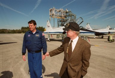 Center Director Roy Bridges (right) welcomes STS-99 Commander Kevin Kregel (left) and the rest of the crew after their arrival at KSC's Shuttle Landing Facility. Behind them are the T-38 jets that transported the crew, with the mate/demate tower in the background. Over the next few days, the crew will review mission procedures, conduct test flights in the Shuttle Training Aircraft and undergo routine preflight medical exams. STS-99 is the Shuttle Radar Topography Mission, which will chart a new course, using two antennae and a 200-foot-long section of space station-derived mast protruding from the payload bay to produce unrivaled 3-D images of the Earth's surface. The result of the Shuttle Radar Topography Mission could be close to 1 trillion measurements of the Earth's topography. Besides contributing to the production of better maps, these measurements could lead to improved water drainage modeling, more realistic flight simulators, better locations for cell phone towers, and enhanced navigation safety. Launch of Endeavour is scheduled for Jan. 31 at 12:47 p.m. EST