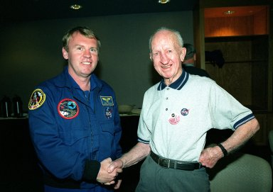 Astronaut Andy Thomas (left) greets 100-year-old Captain Ralph Charles, one of the VIPs attending the launch of STS-99. Charles also met NASA Administrator Dan Goldin. An aviator who has the distinction of being the oldest licensed pilot in the United States, Charles is still flying. He has experienced nearly a century of flight history, from the Wright Brothers to the Space Program. He took flying lessons from one of the first fliers trained by Orville Wright, first repaired then built airplanes, went barnstorming, operated a charter service in the Caribbean, and worked as a test pilot for the Curtiss Wright Airplane Co. Charles watches all the Shuttle launches from his home in Ohio and his greatest wish is to be able to watch one in person from KSC