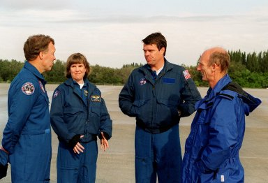 On the runway at the Shuttle Landing Facility, STS-99 crew members Pilot Dominic Gorie, Mission Specialist Janice Voss, Commander Kevin Kregel and Mission Specialist Gerhard Thiele discuss departure plans to Houston. Kregel and Gorie will be piloting T-38 jets with Voss and Thiele as passengers. During the Jan. 31 launch countdown, Endeavour's enhanced master events controller (E-MEC) No. 2 failed a standard preflight test. Launch was postponed and Shuttle managers decided to replace the E-MEC located in the orbiter's aft compartment. Launch controllers will be in a position to begin the STS-99 countdown the morning of Feb. 6 and ready to support a launch midto latenext week pending availability of the Eastern Range. The postponed launch gives the crew an opportunity for more training and time with their families. Known as the Shuttle Radar Topography Mission, it will chart a new course to produce unrivaled 3-D images of the Earth's surface, using two antennae and a 200-foot-long section of space station-derived mast protruding from the payload bay. The result could be close to 1 trillion measurements of the Earth's topography. Besides contributing to the production of better maps, these measurements could lead to improved water drainage modeling, more realistic flight simulators, better locations for cell phone towers, and enhanced navigation safety