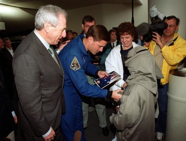 NASA Administrator Dan Goldin (left) watches as 10-year-old Jonathan Pierce (right), who is garbed in a protective cooling suit designed by NASA, shakes hands with astronaut Dog Wheelock. Behind Jonathan is his mother, Penny. Jonathan suffers from erythropoietic protoporphyria, a rare condition that makes his body unable to withstand ultraviolet rays. The suit allows him to be outside during the day, which would otherwise be impossible. Jonathan's trip was funded by the Make-A-Wish Foundation and included a visit to Disney World. He and his family were among a dozen VIPs at KSC to view the launch of STS-99