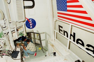 KENNEDY SPACE CENTER, FLA. -- Technicians work in the aft compartment of Shuttle Endeavour's payload bay, where a new Enhanced Main Events Controller (E-MEC) will be installed. The original E-MEC in Endeavour became suspect during the Jan. 31 launch countdown and mission STS-99 was delayed when NASA managers decided to replace it. Each Shuttle carries two enhanced master events controllers (E-MECs), which provide relays for onboard flight computers to send signals to arm and fire pyrotechnics that separate the solid rockets and external tank during assent. Both E-MECs are needed for the Shuttle to be cleared for flight. Currently Endeavour and Columbia are the only two orbiters with the E-MECs. Built by Rockwell's Satellite Space Electronics Division, Anaheim, Calif., each unit weighs 65 pounds and is approximately 20 inches long, 13 inches wide and 8 inches tall. Previously, three Shuttle flights have been scrubbed or delayed due to faulty MECs: STS-73, STS-49 and STS-41-D. Before workers can begin E-MEC replacement efforts at the launch pad, cryogenic reactants had to be offloaded from the orbiter and Space Shuttle ordnance disconnected. The next scheduled date for launch of STS-99 is Feb. 11 at 12:30 p.m. EST