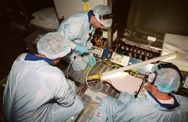 During a Multi-Equipment Interface Test (MEIT) in the U.S. Lab Destiny, which is in the Space Station Processing Facility, astronaut James Voss (left) joins STS-98 Pilot Mark Polansky (center) and Commander Kenneth D. Cockrell (right) in checking wiring against documentation on the floor. Also participating in the MEIT is Mission Specialist Thomas D. Jones (Ph.D.). Voss is assigned to mission STS-102 as part of the second crew to occupy the International Space Station. During the STS-98 mission, the crew will install the Lab on the station during a series of three space walks. The mission will provide the station with science research facilities and expand its power, life support and control capabilities. The U.S. Laboratory Module continues a long tradition of microgravity materials research, first conducted by Skylab and later Shuttle and Spacelab missions. Destiny is expected to be a major feature in future research, providing facilities for biotechnology, fluid physics, combustion, and life sciences research. The Lab is planned for launch aboard Space Shuttle Atlantis on the sixth ISS flight, currently targeted no earlier than Aug. 19, 2000