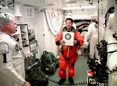 STS-99 Mission Specialist Mamoru Mohri of Japan holds a memento from friends before entering orbiter Endeavour. With him are members of the White Room closeout crew, Chris Meinert (left), closeout chief, and Jack Burritt (background), Quality Assurance specialist. The White Room is an environmental chamber at the end of the orbiter access arm, on the fixed service structure, that provides entry to the orbiter crew compartment. STS-99, known as the Shuttle Radar Topography Mission (SRTM), will chart a new course to produce unrivaled 3-D images of the Earth's surface. The result of the Shuttle Radar Topography Mission could be close to 1 trillion measurements of the Earth's topography. Scheduled for liftoff at 12:30 p.m. EST, the mission is expected to last 11days, with Endeavour landing at KSC Tuesday, Feb. 22, at 4:36 p.m. EST. This is the 97th Shuttle flight and 14th for Shuttle Endeavour