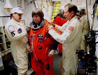 Before entering the orbiter Endeavour, STS-99 Mission Specialist Janice Voss is helped by Travis Thompson and Jack Burritt, members of the White Room closeout crew. The White Room is an environmental chamber at the end of the orbiter access arm, on the fixed service structure, that provides entry to the orbiter crew compartment. STS-99, known as the Shuttle Radar Topography Mission (SRTM), will chart a new course to produce unrivaled 3-D images of the Earth's surface. The result of the Shuttle Radar Topography Mission could be close to 1 trillion measurements of the Earth's topography. Scheduled for liftoff at 12:30 p.m. EST, the mission is expected to last 11days, with Endeavour landing at KSC Tuesday, Feb. 22, at 4:36 p.m. EST. This is the 97th Shuttle flight and 14th for Shuttle Endeavour