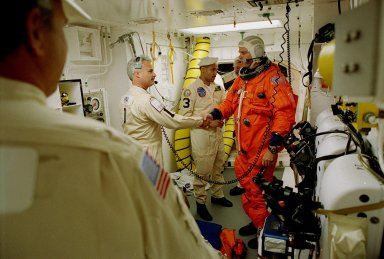 Before entering the orbiter Endeavour, STS-99 Commander Kevin Kregel shakes hands with Chris Meinert, closeout chief of the White Room closeout crew. In the background is Carlos Gillis, suit technician. The White Room is an environmental chamber at the end of the orbiter access arm, on the fixed service structure, that provides entry to the orbiter crew compartment. STS-99, known as the Shuttle Radar Topography Mission (SRTM), will chart a new course to produce unrivaled 3-D images of the Earth's surface. The result of the Shuttle Radar Topography Mission could be close to 1 trillion measurements of the Earth's topography. Scheduled for liftoff at 12:30 p.m. EST, the mission is expected to last 11days, with Endeavour landing at KSC Tuesday, Feb. 22, at 4:36 p.m. EST. This is the 97th Shuttle flight and 14th for Shuttle Endeav