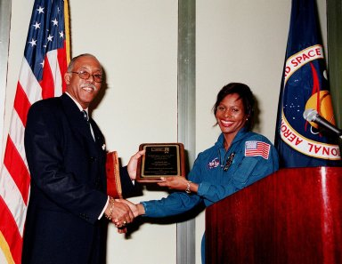 In the Early Space Exploration Conference Center at the KSC Visitor Complex, Dr. Julian M. Earls (left), deputy director for Operations, Glenn Research Center, receives a plaque from astronaut Joan Higginbotham (right) during the 2000 African American History Month Celebration Luncheon. Dr. Earls was guest speaker at the luncheon