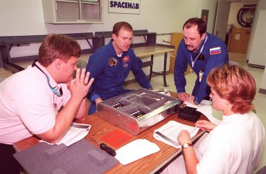 KENNEDY SPACE CENTER, FLA. -- At SPACEHAB, in Cape Canaveral, Fla., members of the STS-101 crew take part in Crew Equipment Interface Test (CEIT) activities, learning about some of the equipment they will be working with on their mission to the International Space Station. Commander James Halsell and Mission Specialist Yuri Usachev of Russia look over a biotube precursor in front of them with (left) Dan Shultz of NASA's Flight Experiments Mission Management Office and (right) April Boody of Bionetics. Other members of the crew (not shown) taking part in the CEIT are Pilot Scott Horowitz and Mission Specialists Mary Ellen Weber, James Voss, Jeffrey Williams and Susan Helms. The crew will be responsible for preparing the Space Station for the arrival of the Zvezda Service Module, expected to be launched by Russia in July 2000. Also, the crew will conduct one space walk to perform maintenance on the Space Station and deliver logistics and supplies. This will be the third assembly flight for the Space Station. STS-101 is scheduled to launch no earlier than April 13 from Launch Pad 39A