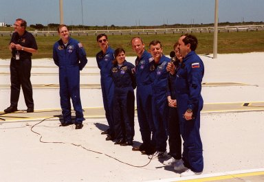 """KENNEDY SPACE CENTER, Fla. -- After Terminal Countdown Demonstration Test (TCDT) activities at Launch Pad 39A, the STS-101 crew answers questions from the media. From left to right are moderator George Diller, with NASA Public Affairs; Commander James D. Halsell Jr. ; Pilot Scott J. """"Doc"""" Horowitz and Mission Specialists Mary Ellen Weber, Jeffrey N. Williams, James S. Voss, Susan J. Helms and Yury Usachev of Russia, with the microphone. The TCDT includes emergency egress training and a simulated launch countdown. During their mission to the International Space Station, the STS-101 crew will be delivering logistics and supplies, plus preparing the Station for the arrival of the Zvezda Service Module, expected to be launched by Russia in July 2000. Also, the crew will conduct one space walk to perform maintenance on the Space Station. This will be the third assembly flight for the Space Station. STS-101 is scheduled to launch April 24 at 4:15 p.m. from Launch Pad 39A"""