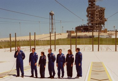 """KENNEDY SPACE CENTER, Fla. -- After Terminal Countdown Demonstration Test (TCDT) activities at Launch Pad 39A, the STS-101 crew talk to the media. At the microphone is Commander James D. Halsell Jr. Next to him, standing left to right, are Pilot Scott J. """"Doc"""" Horowitz and Mission Specialists Mary Ellen Weber, Jeffrey N. Williams, James Voss, Susan J. Helms and Yury Usachev of Russia. The TCDT includes emergency egress training and a simulated launch countdown. During their mission to the International Space Station, the STS-101 crew will be delivering logistics and supplies, plus preparing the Station for the arrival of the Zvezda Service Module, expected to be launched by Russia in July 2000. Also, the crew will conduct one space walk to perform maintenance on the Space Station. This will be the third assembly flight for the Space Station. STS-101 is scheduled to launch April 24 at 4:15 p.m. from Launch Pad 39A"""