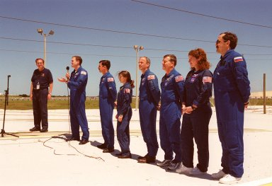 """KENNEDY SPACE CENTER, Fla. -- After Terminal Countdown Demonstration Test (TCDT) activities at Launch Pad 39A, the STS-101 crew talk to the media. At the far left is George Diller, with NASA Public Affairs, who is moderating the event. At the microphone Commander James D. Halsell Jr. answers a question. Next to him, standing left to right, are Pilot Scott J. """"Doc"""" Horowitz and Mission Specialists Mary Ellen Weber, Jeffrey N. Williams, James Voss, Susan J. Helms and Yury Usachev of Russia. The TCDT includes emergency egress training and a simulated launch countdown. During their mission to the International Space Station, the STS-101 crew will be delivering logistics and supplies, plus preparing the Station for the arrival of the Zvezda Service Module, expected to be launched by Russia in July 2000. Also, the crew will conduct one space walk to perform maintenance on the Space Station. This will be the third assembly flight for the Space Station. STS-101 is scheduled to launch April 24 at 4:15 p.m. from Launch Pad 39A"""