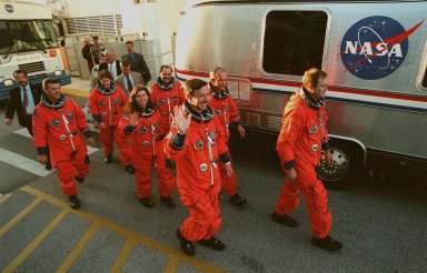 """The STS-101 crew wave at onlookers as they walk from the Operations and Checkout Building to the Astrovan, which will take them to Space Shuttle Atlantis on Launch Pad 39A for a simulated countdown exercise. Leading the way are (left) Pilot Scott J. """"Doc"""" Horowitz and (right) Commander James D. Halsell Jr. In the second row are Mission Specialists (left) Mary Ellen Weber and (right) Jeffrey N. Williams. In the third row are Mission Specialists (left) James Voss, (waving) Susan J. Helms, and (right) Yury Usachev of Russia. The dress rehearsal for launch is part of Terminal Countdown Demonstration Test (TCDT) activities that include emergency egress training and familiarization with the payload. During their mission to the International Space Station, the STS-101 crew will be delivering logistics and supplies, plus preparing the Station for the arrival of the Zvezda Service Module, expected to be launched by Russia in July 2000. Also, the crew will conduct one space walk to perform maintenance on the Space Station. This will be the third assembly flight for the Space Station. STS-101 is scheduled to launch April 24 at 4:15 p.m. from Launch Pad 39A"""