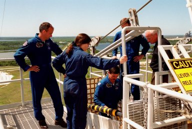 """KENNEDY SPACE CENTER, Fla. -- During emergency egress training at Launch pad 39A, STS-101 Mission Specialists Jeffrey N. Williams and Mary Ellen Weber, Pilot Scott J. """"Doc"""" Horowitz and Commander James D. Halsell Jr. get instruction on using the slidewire basket. The basket would be used in the event the crew needed to exit quickly from the fixed service structure at the 195-foot level. The training is part of Terminal Countdown Demonstration Test (TCDT) activities that include a simulated launch countdown and familiarization with the payload. Others taking part in the TCDT are Mission Specialists James Voss, Susan J. Helms and Yury Usachev of Russia. During their mission to the International Space Station, the STS-101 crew will be delivering logistics and supplies, plus preparing the Station for the arrival of the Zvezda Service Module, expected to be launched by Russia in July 2000. Also, the crew will conduct one space walk to perform maintenance on the Space Station. This will be the third assembly flight for the Space Station. STS-101 is scheduled to launch April 24 at 4:15 p.m. from Launch Pad 39A"""