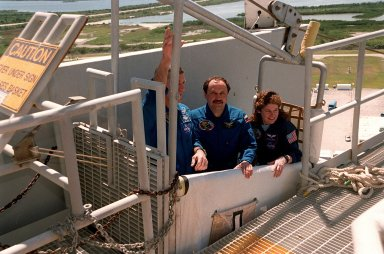 """KENNEDY SPACE CENTER, Fla. -- During emergency egress training at Launch pad 39A, STS-101 Mission Specialists James Voss, Yury Usachev of Russia, and Susan J. Helms test the slidewire basket that they would use if needed to exit quickly from the fixed service structure at the 195-foot level. The training is part of Terminal Countdown Demonstration Test (TCDT) activities that include a simulated launch countdown and familiarization with the payload. Others taking part in the TCDT are Commander James D. Halsell Jr., Pilot Scott J. """"Doc"""" Horowitz, and Mission Specialists Mary Ellen Weber and Jeffrey N. Williams. During their mission to the International Space Station, the STS-101 crew will be delivering logistics and supplies, plus preparing the Station for the arrival of the Zvezda Service Module, expected to be launched by Russia in July 2000. Also, the crew will conduct one space walk to perform maintenance on the Space Station. This will be the third assembly flight for the Space Station. STS-101 is scheduled to launch April 24 at 4:15 p.m. from Launch Pad 39A"""