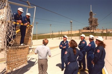 """KENNEDY SPACE CENTER, Fla. -- During emergency egress training at Launch pad 39A, STS-101 Pilot Scott J. """"Doc"""" Horowitz and Mission Specialist Yury Usachev stand in the slidewire basket at the landing zone. The Safety Egress officer (left on ground) provides training on use of the basket in the event the crew needed to exit quickly from the fixed service structure (background) at the 195-foot level. The rest of the crew, clockwise at right, are Commander James D. Halsell Jr. and Mission Specialists Jeffrey N. Williams, James Voss, Susan Helms, and (back to the camera) Mary Ellen Weber. The training is part of Terminal Countdown Demonstration Test (TCDT) activities that include a simulated launch countdown and familiarization with the payload. During their mission to the International Space Station, the STS-101 crew will be delivering logistics and supplies, plus preparing the Station for the arrival of the Zvezda Service Module, expected to be launched by Russia in July 2000. Also, the crew will conduct one space walk to perform maintenance on the Space Station. This will be the third assembly flight for the Space Station. STS-101 is scheduled to launch April 24 at 4:15 p.m. from Launch Pad 39A"""