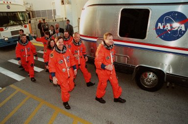 """The STS-101 crew walk from the Operations and Checkout Building to the Astrovan, which will take them to Space Shuttle Atlantis on Launch Pad 39A for a simulated countdown exercise. Leading the way are (left) Pilot Scott J. """"Doc"""" Horowitz and (right) Commander James D. Halsell Jr. In the second row are Mission Specialists (left) Mary Ellen Weber and (right) Jeffrey N. Williams. In the third row are Mission Specialists (left) James Voss, (waving) Susan J. Helms, and (right) Yury Usachev of Russia. The dress rehearsal for launch is part of Terminal Countdown Demonstration Test (TCDT) activities that include emergency egress training and familiarization with the payload. During their mission to the International Space Station, the STS-101 crew will be delivering logistics and supplies, plus preparing the Station for the arrival of the Zvezda Service Module, expected to be launched by Russia in July 2000. Also, the crew will conduct one space walk to perform maintenance on the Space Station. This will be the third assembly flight for the Space Station. STS-101 is scheduled to launch April 24 at 4:15 p.m. from Launch Pad 39A"""