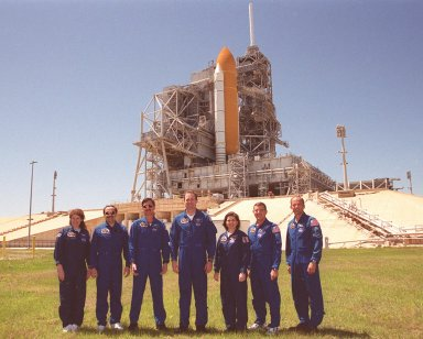 """KENNEDY SPACE CENTER, Fla. -- During a break in their Terminal Countdown Demonstration Test (TCDT), the STS-101 crew poses in front of Space Shuttle Atlantis at Launch Pad 39A. Standing, left to right, are Mission Specialists Susan J. Helms and Yury Usachev of Russia; Pilot Scott J. """"Doc"""" Horowitz; Commander James D. Halsell Jr.; and Mission Specialists Mary Ellen Weber, James Voss and Jeffrey N. Williams. The TCDT includes emergency egress training and a simulated launch countdown. During their mission to the International Space Station, the STS-101 crew will be delivering logistics and supplies, plus preparing the Station for the arrival of the Zvezda Service Module, expected to be launched by Russia in July 2000. Also, the crew will conduct one space walk to perform maintenance on the Space Station. This will be the third assembly flight for the Space Station. STS-101 is scheduled to launch April 24 at 4:15 p.m. from Launch Pad 39A"""