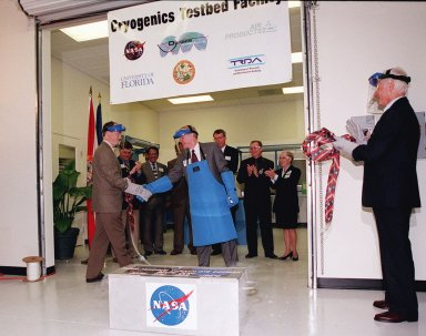 """Center Director Roy Bridges (center) is congratulated for the successful breaking of the ceremonial """"ribbon"""" and the opening of the new Cryogenic Testbed Facility. Part of the normal ribbon was replaced with plastic tubing and frozen in liquid nitrogen for the event. Bridges hit the tubing with a small hammer to break it. The Cryogenics Testbed was built to provide cryogenics engineering development and testing services to meet the needs of industry. It will also support commercial, government and academic customers for technology development initiatives on the field of cryogenics. The facility is jointly managed by NASA and Dynacs Engineering Co. , NASA/SC's Engineering Development contractor"""