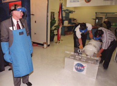 """Center Director Roy Bridges (left), wearing protective apron, gloves and face shield, watches as liquid nitrogen is poured into a container to freeze the plastic tubing for a special """"ribbon-breaking"""" to open the new Cryogenic Testbed Facility. Bridges hit the section of tubing with a small hammer to break it. The Cryogenics Testbed was built to provide cryogenics engineering development and testing services to meet the needs of industry. It will also support commercial, government and academic customers for technology development initiatives on the field of cryogenics. The facility is jointly managed by NASA and Dynacs Engineering Co. , NASA/SC's Engineering Development contractor"""